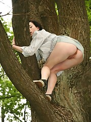 Doll in skirt climbs up the tree and has her cunt bared